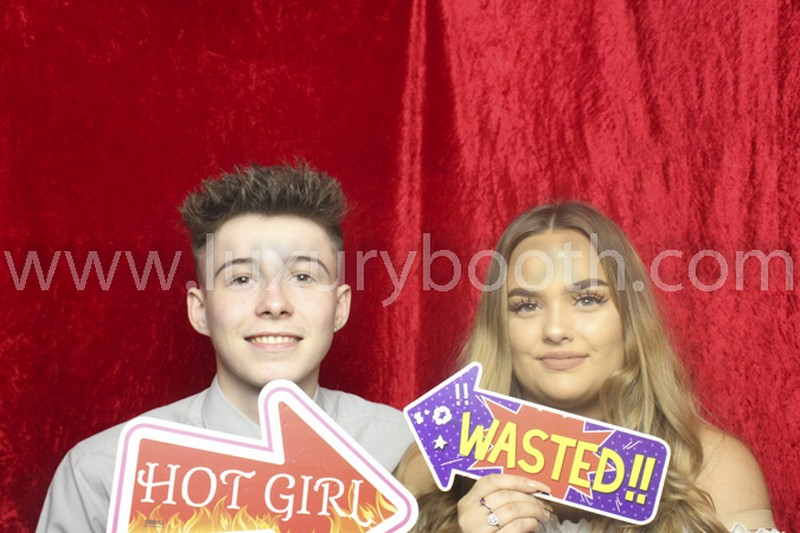 2 guests in a photo booth with prop signs