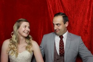 Bride and groom in a photo booth sharing a joke - wedding celebrations at Taunton Rugby Club